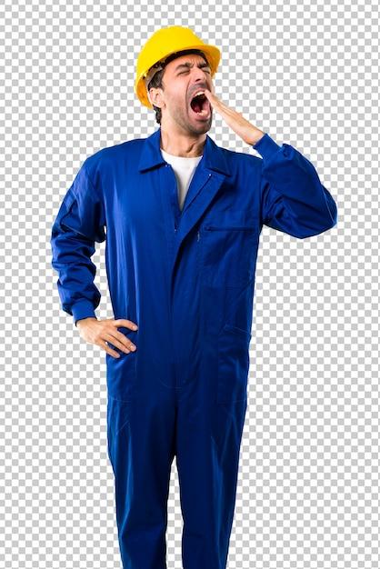 Jeune ouvrier avec casque bâillant et couvrant la bouche grande ouverte avec la main. expression endormie PSD Premium
