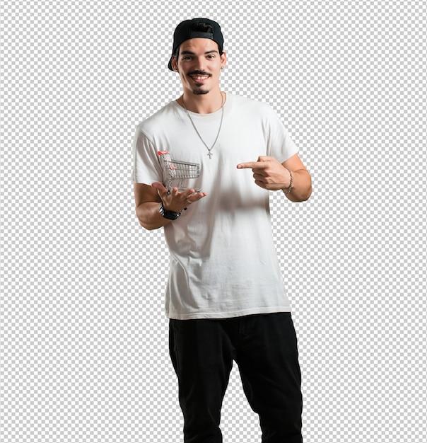Jeune rappeur, homme souriant et heureux, tenant un caddie miniature, concept de shopping PSD Premium