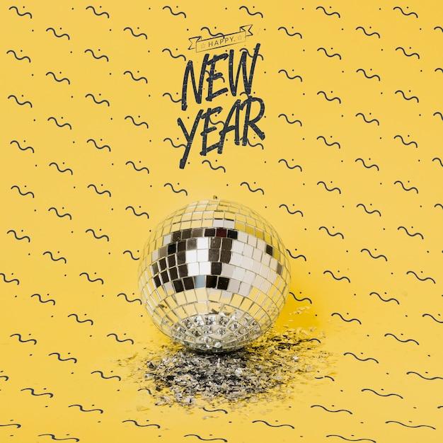 Lettrage du nouvel an à côté du bal disco Psd gratuit