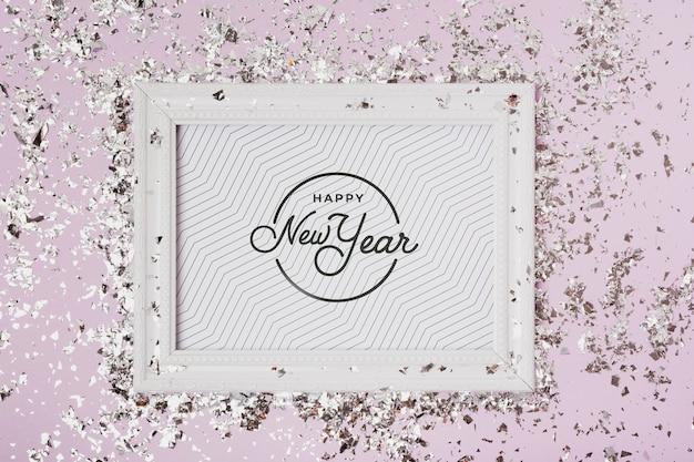 Lettrage du nouvel an sur maquette de cadre avec des confettis Psd gratuit