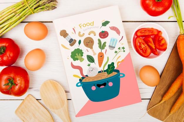 Livre de menu de nourriture entouré d'œufs et de tomates Psd gratuit