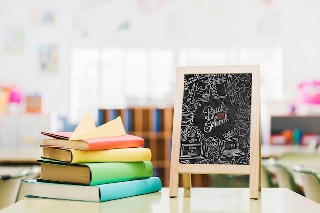Livres colorés à côté de la maquette du tableau d'école Psd gratuit