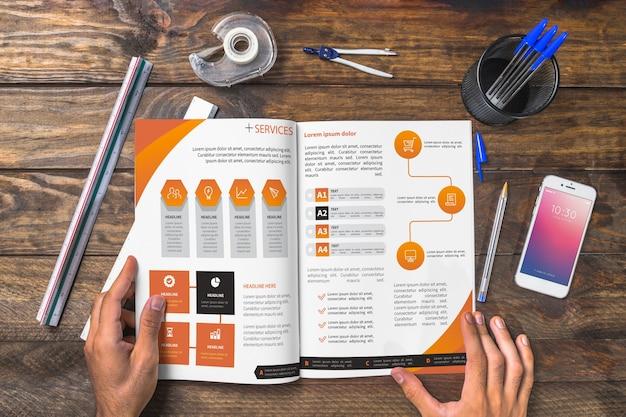Magazine et maquette de smartphone sur une table en bois avec des stylos et des règles Psd gratuit