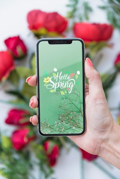 Main tenant la maquette du smartphone au-dessus des fleurs Psd gratuit
