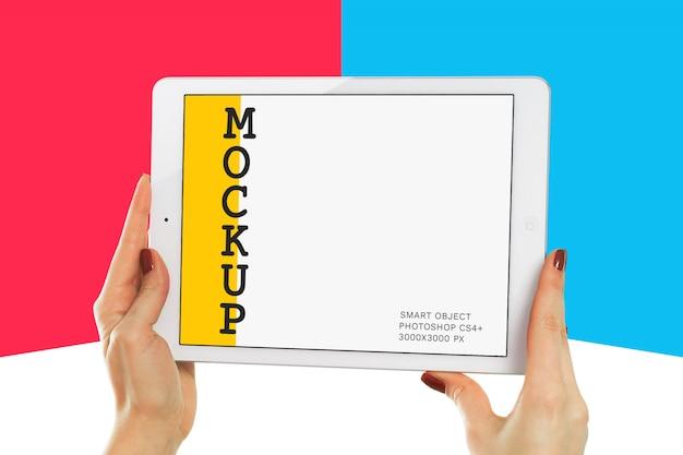 Main tenant la maquette de la tablette blanche PSD Premium