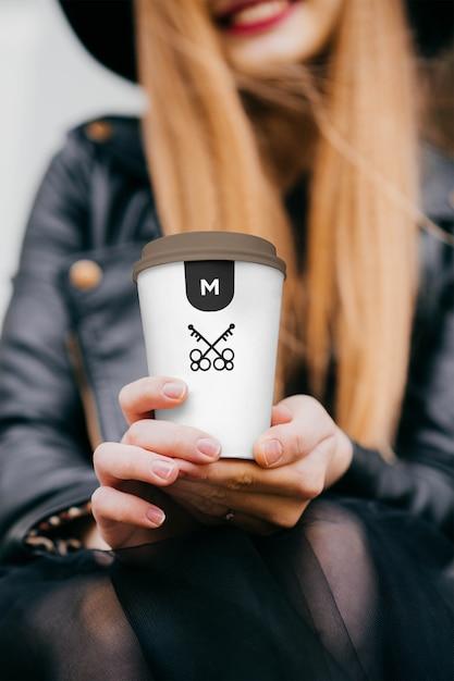 Main tenant la maquette de la tasse à café PSD Premium