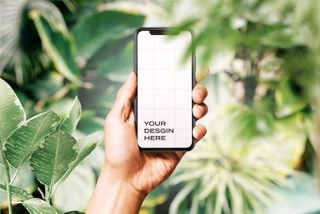 Main Tenant Une Nouvelle Maquette De Smartphone Entourée De Feuilles PSD Premium