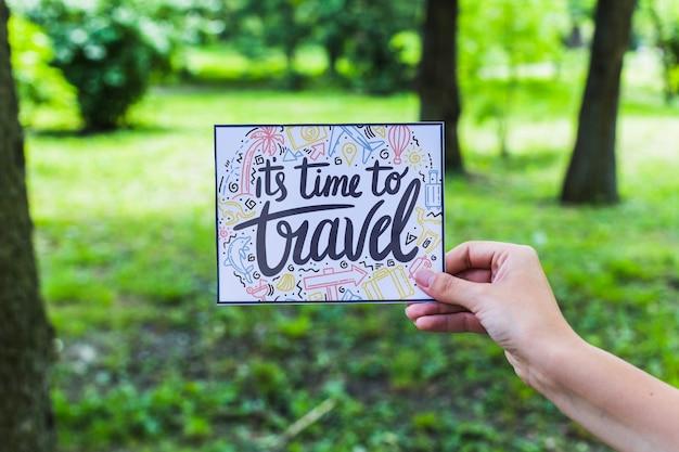 Main tenant le papier dans la nature pour le concept de voyage Psd gratuit