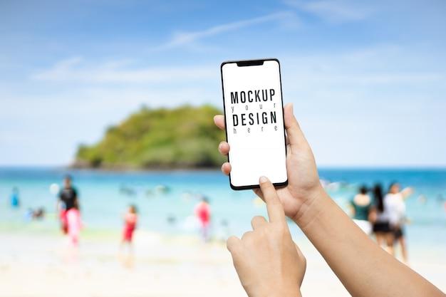 Main tenant un téléphone intelligent en face de la plage PSD Premium
