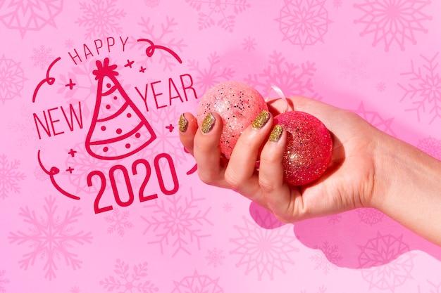 Main Vue De Face Tenant Des Boules De Noël Avec Des Paillettes Psd gratuit