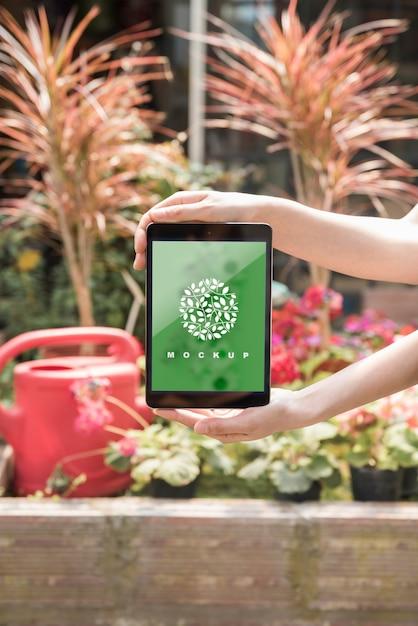 Mains sur maquette de tablette avec concept de jardinage Psd gratuit