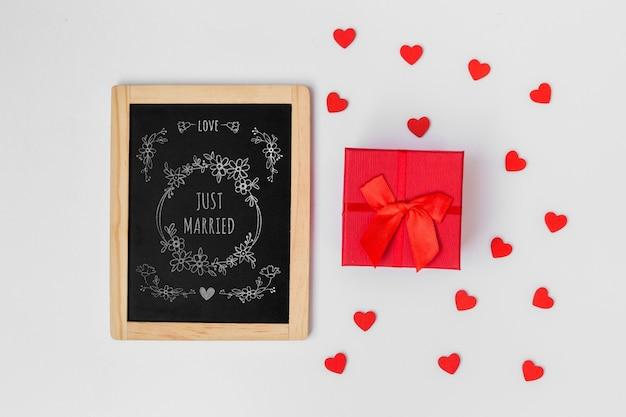 Maquette en ardoise à côté d'un coffret pour la saint-valentin Psd gratuit