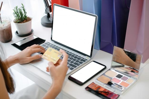 Maquette de belle femme détenant la carte de crédit en appréciant dans le site de shopping en ligne avec smartphone et ordinateur portable PSD Premium