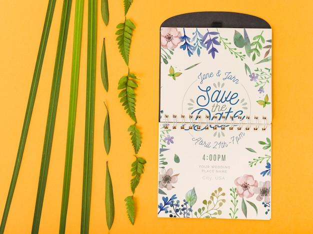 Maquette bloc-notes avec des feuilles tropicales Psd gratuit