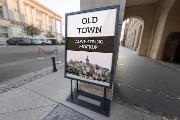 Maquette de cadre de publicité noir classique en plein air vertical vertical sur le vieux trottoir PSD Premium