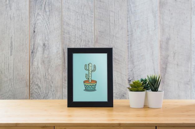 Maquette de cadre sur table avec des plantes Psd gratuit