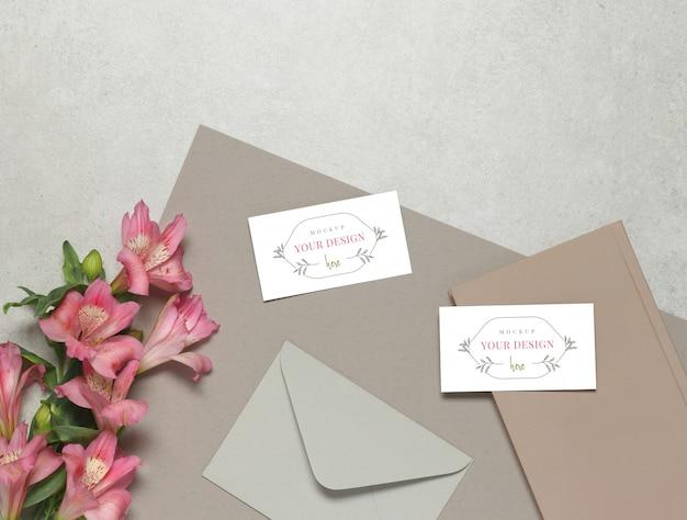 Maquette carte de visite sur fond gris, fleurs fraîches, enveloppe grise et notes roses PSD Premium