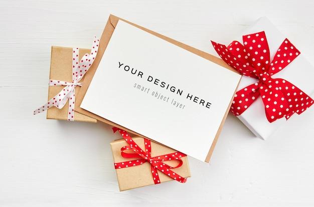 Maquette De Carte De Voeux Avec Enveloppe Et Coffrets Cadeaux Sur Fond De Bois Blanc PSD Premium