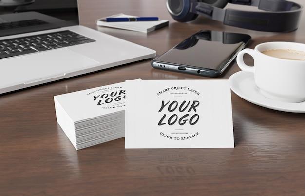 Maquette de cartes de visite sur un bureau en bois avec rendu 3d des éléments du bureau PSD Premium