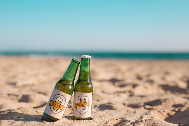 Maquette de deux bouteilles de bière à la plage Psd gratuit