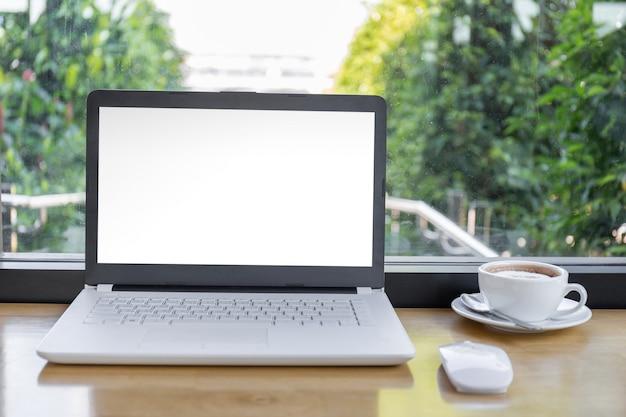 Maquette écran blanc de l'ordinateur portable avec une tasse de café sur une table en bois avec un tracé de détourage arrière-plan flou. PSD Premium