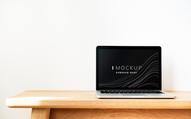 Maquette d'écran d'ordinateur portable sur une table en bois PSD Premium