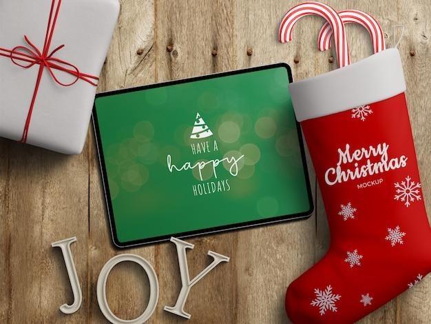 Maquette De L'écran De La Tablette Et Chaussette De Stockage Avec Décoration De Noël Sur Table En Bois PSD Premium