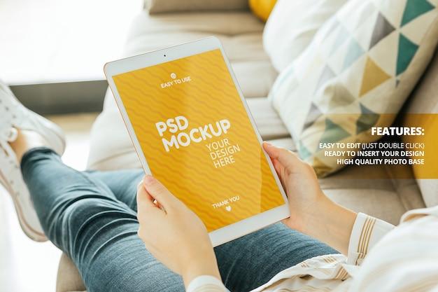 Maquette D'écran De Tablette Tenue Par Une Femme Assise Sur Le Canapé PSD Premium