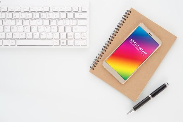 Maquette écran vide de smartphone sur ordinateur portable avec un stylo et clavier d'ordinateur sur blanc PSD Premium