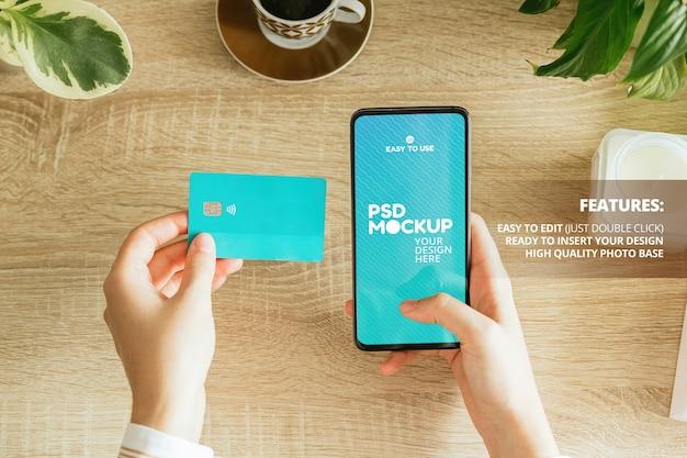 Maquette D'une Femme Tenant Un Téléphone Et Une Carte De Crédit Sur La Table PSD Premium