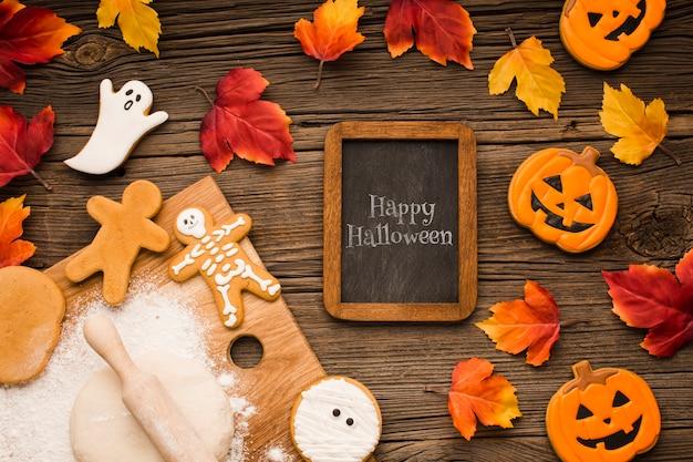 Maquette avec friandises d'halloween et feuilles d'automne Psd gratuit
