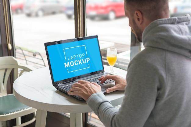Maquette D'ordinateur Portable Gérée Par Un Pigiste Dans Un Café PSD Premium