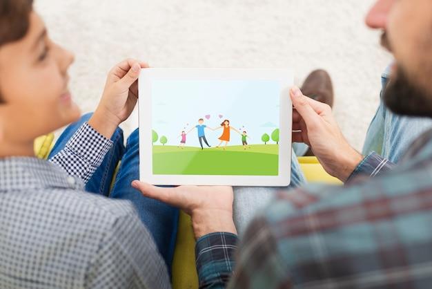 Maquette père et fils en regardant sur une tablette Psd gratuit
