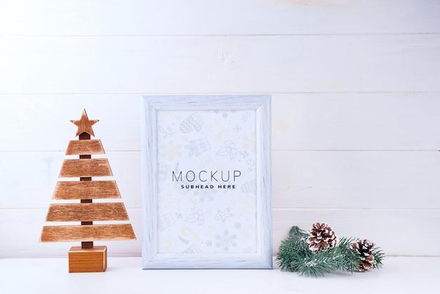 Maquette Photo Avec Cadre Blanc, Arbre En Bois Et Branches De Pin Sur Fond En Bois Blanc PSD Premium