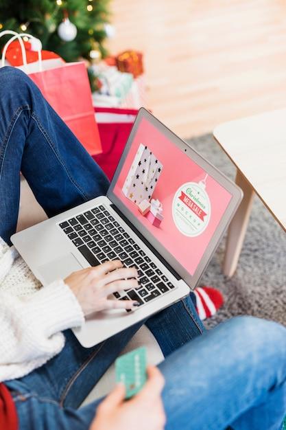 Maquette de vente de noël avec une femme à l'aide d'un ordinateur portable Psd gratuit