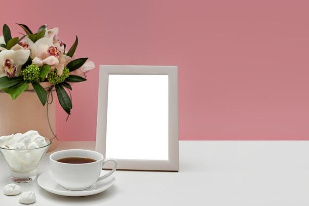Maquette Vierge Vue De Face Du Cadre Photo Sur La Table Rose. Fleurs D'orchidées, Tasse De Thé Et Bonbons. PSD Premium