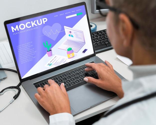 Médecin à L'aide D'une Maquette D'ordinateur Portable PSD Premium
