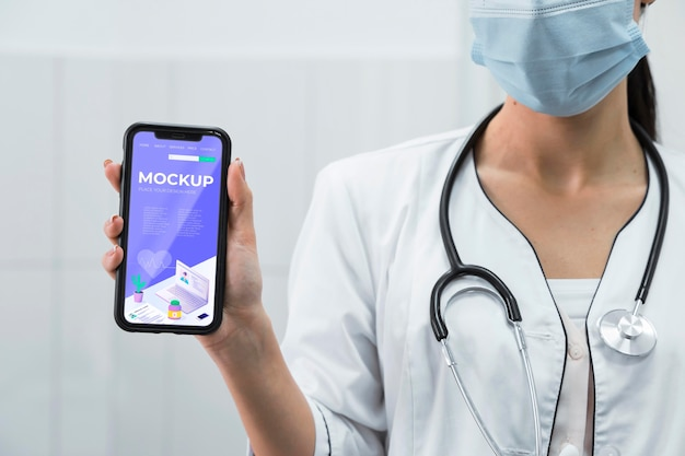 Médecin Avec Masque Facial Tenant Une Maquette De Téléphone Psd gratuit