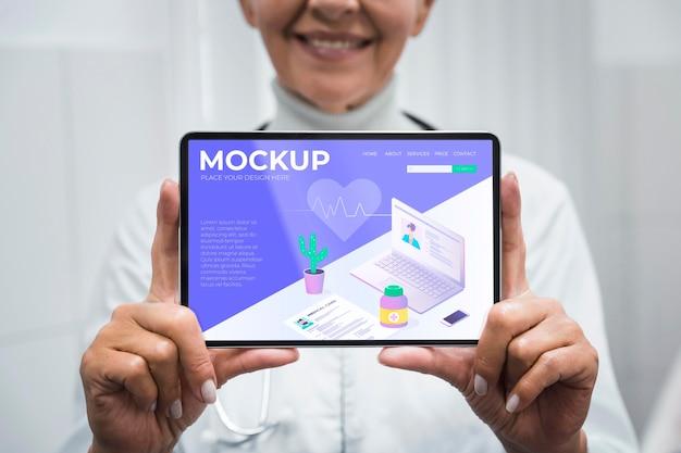 Médecin Tenant Une Maquette De Tablette Psd gratuit