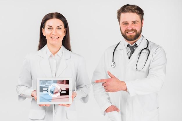 Médecins tenant une maquette de tablette pour la fête du travail Psd gratuit