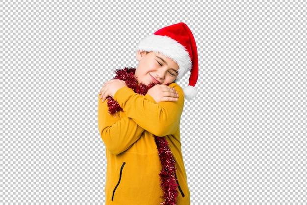 Petit garçon célébrant le jour de noël portant un bonnet de noel isolé câlins, souriant insouciant et heureux. PSD Premium
