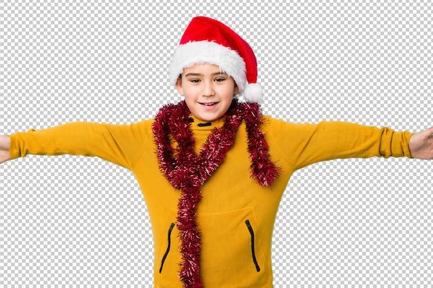 Petit garçon fête le jour de noël portant un bonnet de noel isolé se sent confiant donnant un câlin à la caméra. PSD Premium