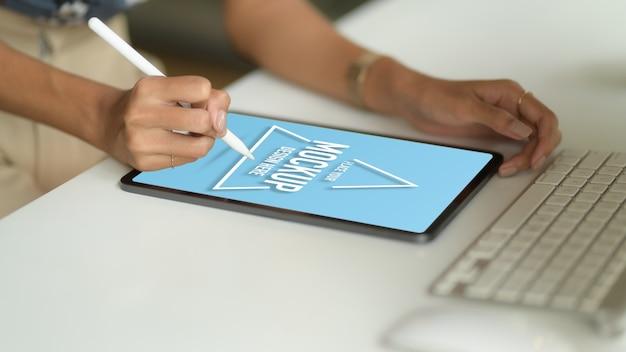Photo Recadrée De Main Féminine Dessin Sur Maquette Tablette Avec Stylet Sur Table D'ordinateur Dans La Salle De Bureau PSD Premium
