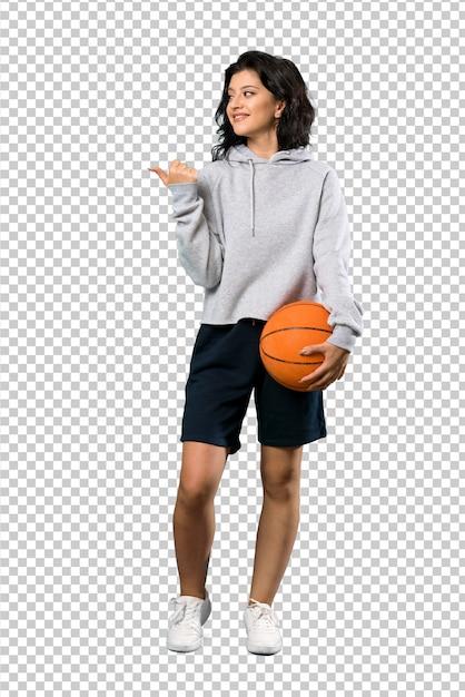 Un Plan Complet D'une Jeune Femme Jouant Au Basketball Pointant Sur Le Côté Pour Présenter Un Produit PSD Premium