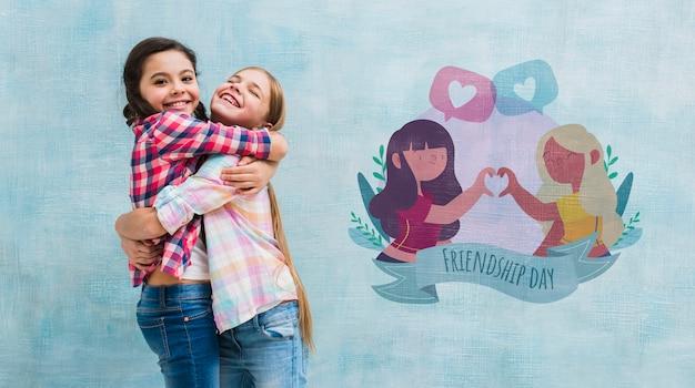 Plan moyen petites filles embrassant avec une maquette de mur Psd gratuit