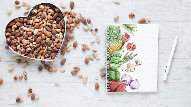 Plat poser des aliments sains avec la maquette du bloc-notes Psd gratuit