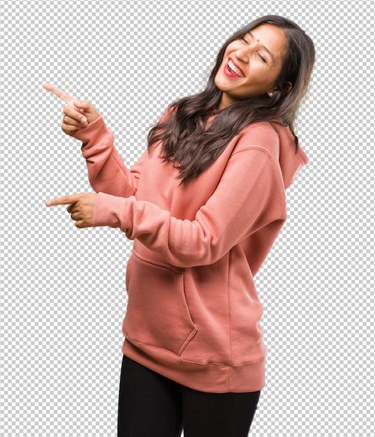 Portrait de jeune femme indienne de fitness pointant sur le côté, souriant surpris présentant quelque chose, naturel et désinvolte PSD Premium