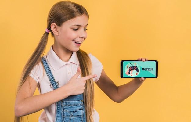 Portrait De Jeune Fille Tenant Un Téléphone Mobile Avec Maquette Psd gratuit