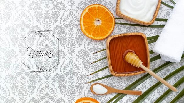 Pose à plat de beurre corporel et de miel avec une tranche d'orange Psd gratuit