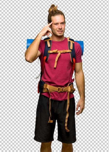 Randonneur homme avec sac à dos montagne faisant le geste de la folie mettant le doigt sur la tête PSD Premium